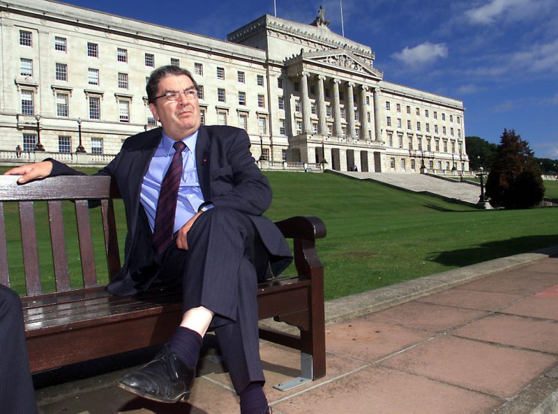 John Hume sits in front of the Stormont Parliament Buildings.