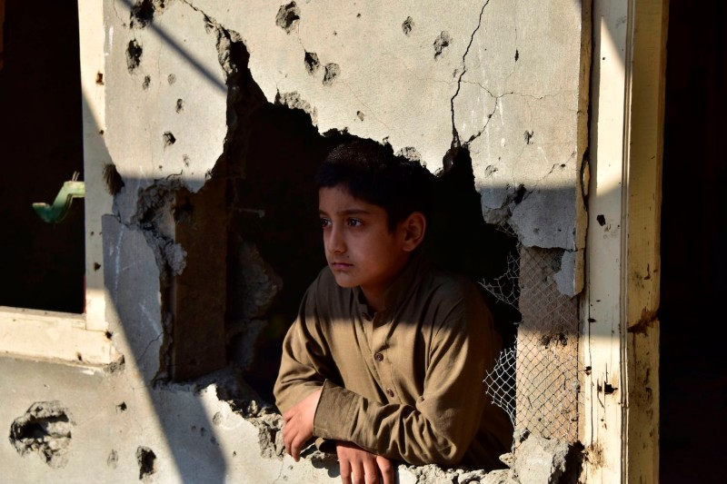 A Kashmiri boy looks out from his damaged family house after cross border shelling.