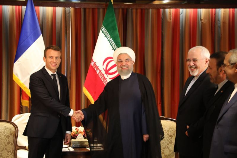 France's President Emmanuel Macron (L) shakes hands with his Iranian counterpart Hassan Rouhani (C) as Iran's foreign minister, Mohammad Javad Zarif (R) and other members of the Iranian delegation stand next to them during an official meeting on September 18, 2017, in New York.