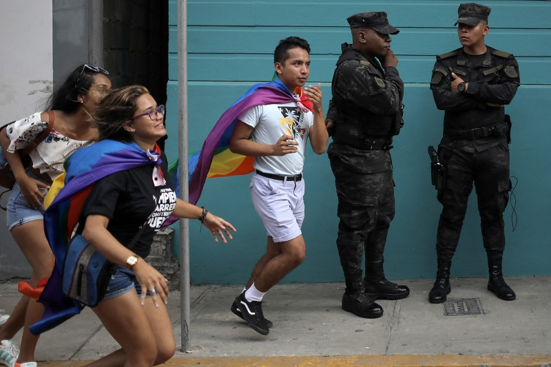 Revelers take part in a Gay Pride Parade in front of policemen in Panama City on June 29, 2019.