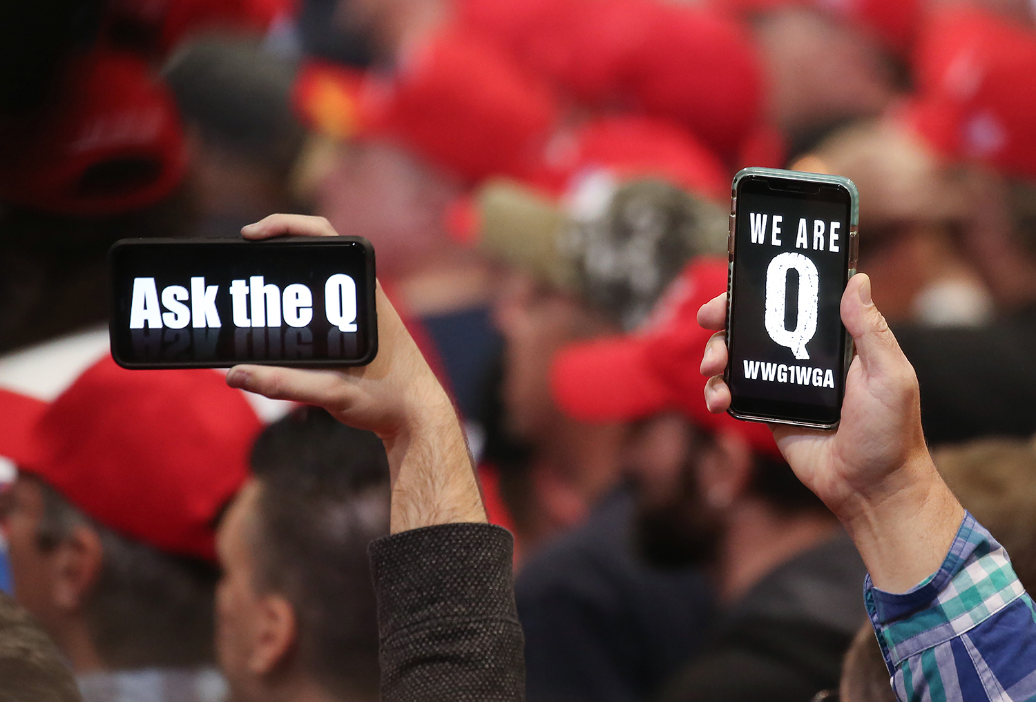 Supporters of President Donald Trump hold up their phones with messages referring to QAnon at a campaign rally at Las Vegas Convention Center in Nevada on Feb. 21.