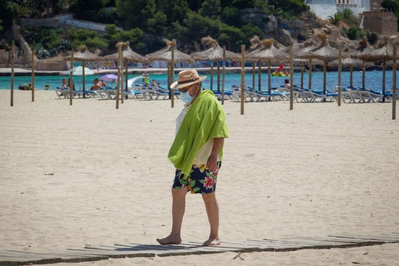 A tourist wearing a face mask walks on Magaluf Beach in Calvia on the Spanish island of Mallorca on July 8.