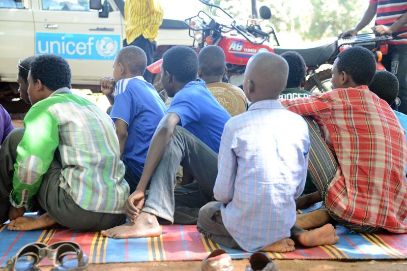 Young fighters sit on a blanket in downtown Bambari after over 350 of Central African Republic's child soldiers were released by armed groups honoring a deal signed with UNICEF, on May 14, 2015.