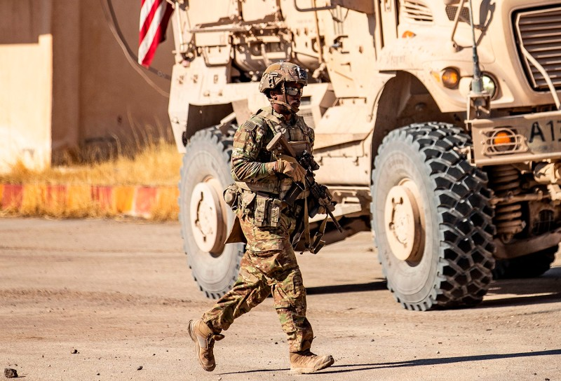 A U.S. soldier walks in front of a military vehicle patroling near the city of Al-Malikiyah in northeastern Syria, near the Turkish border, on Aug. 27.