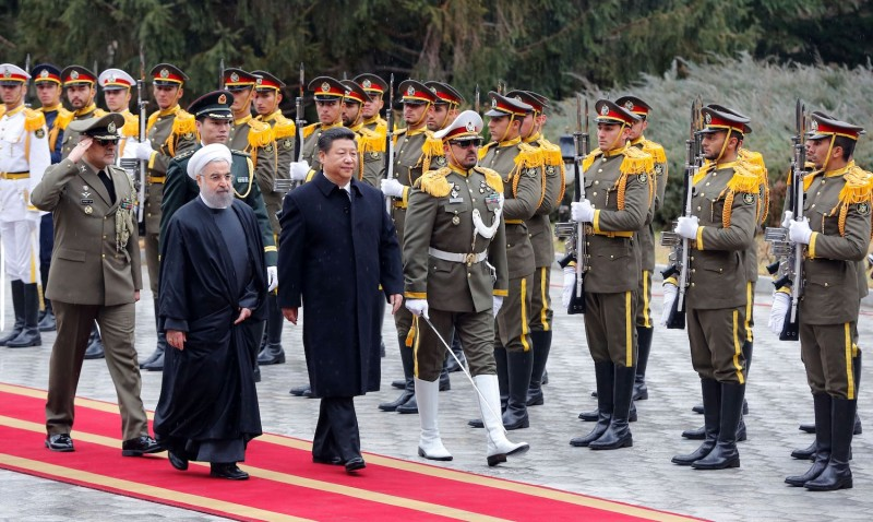 Iranian President Hassan Rouhani and Chinese President Xi Jinping review troops during a welcoming ceremony.