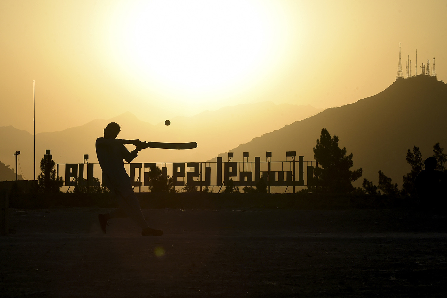 Youths play cricket at sunset at the Nader Khan hilltop in Kabul on Sept. 22. WAKIL KOHSAR/AFP via Getty Images