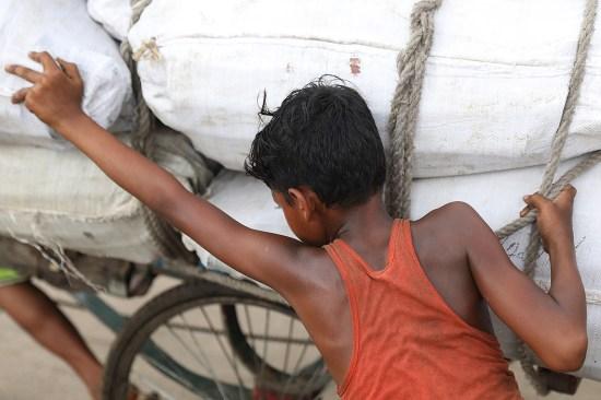 Child laborer Nazmul Hossain, 13, pushes a rickshaw.