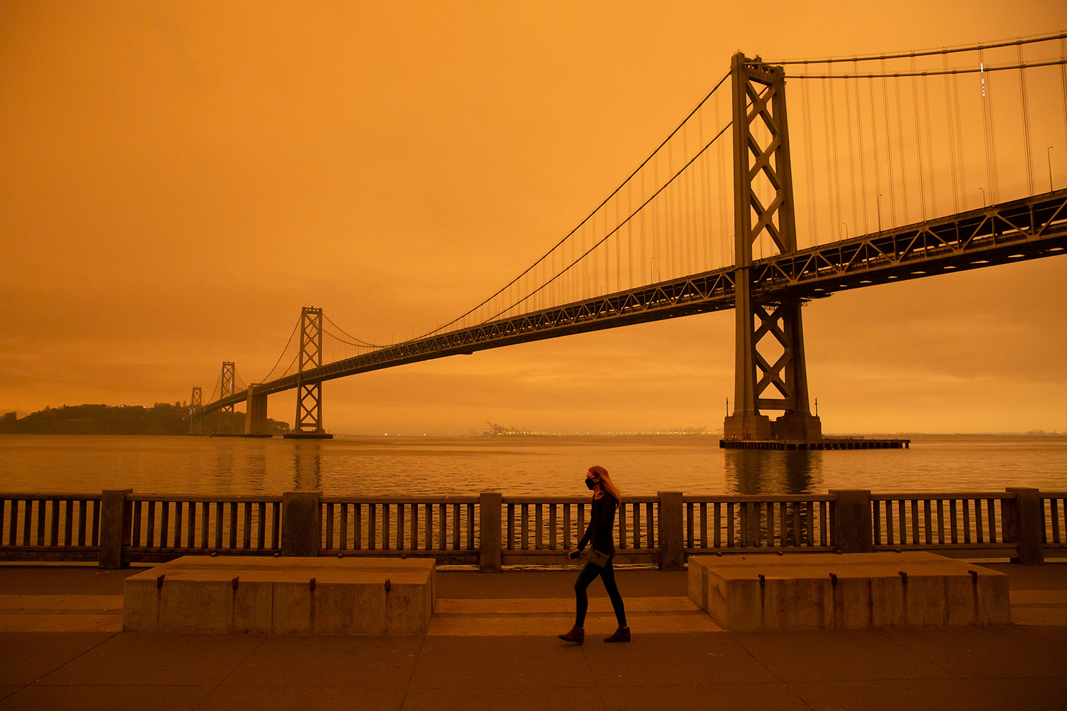 A woman walks along The Embarcadero in San Francisco under an orange smoke-filled sky on Sept. 9. BRITTANY HOSEA-SMALL/AFP via Getty Images