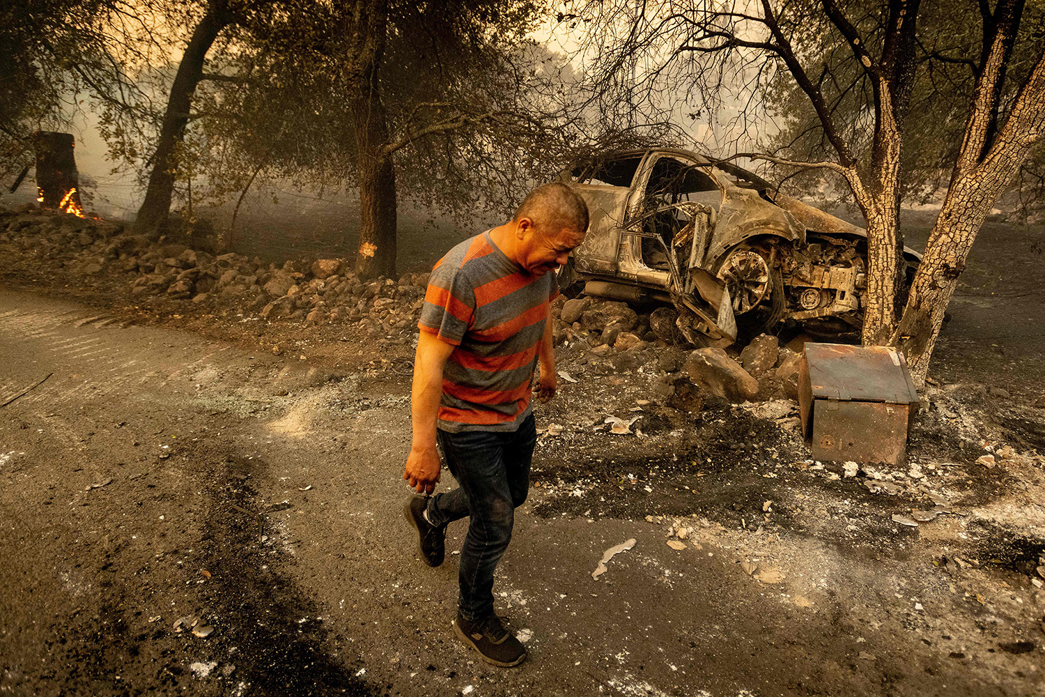 Resident Osvaldo Ramirez walks away from his burned vehicle during the Glass Fire in St. Helena, California, on Sept. 27. Ramirez said the $8,000 in cash along with his family's papers located in a safe inside the vehicle were burned. JOSH EDELSON/AFP via Getty Images