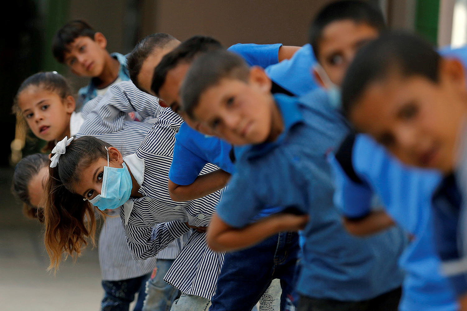 Palestinian students exercise as schools reopen gradually amid the COVID-19 outbreak in the village of Susya in the Israeli-occupied West Bank on Sept. 7. Mussa Qawasma/REUTERS