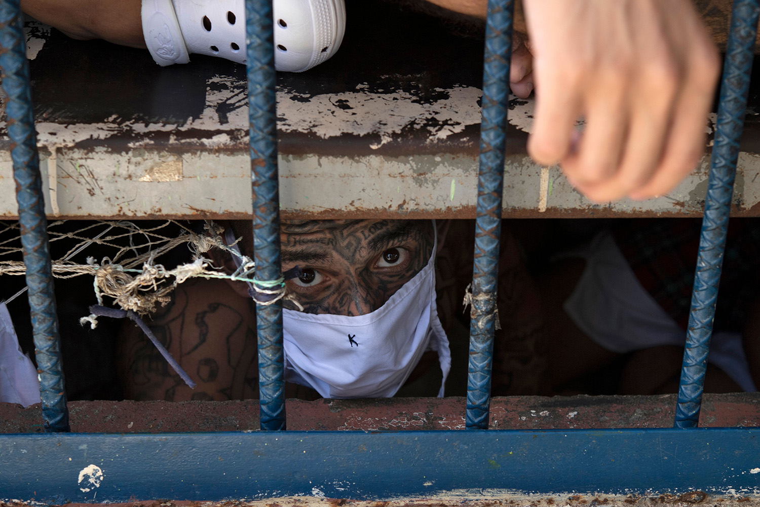 A member of the gang Barrio 18 looks out from an overcrowded cell at the Quezaltepeque prison in Quezaltepeque, El Salvador, on Sept. 4. YURI CORTEZ/AFP via Getty Images