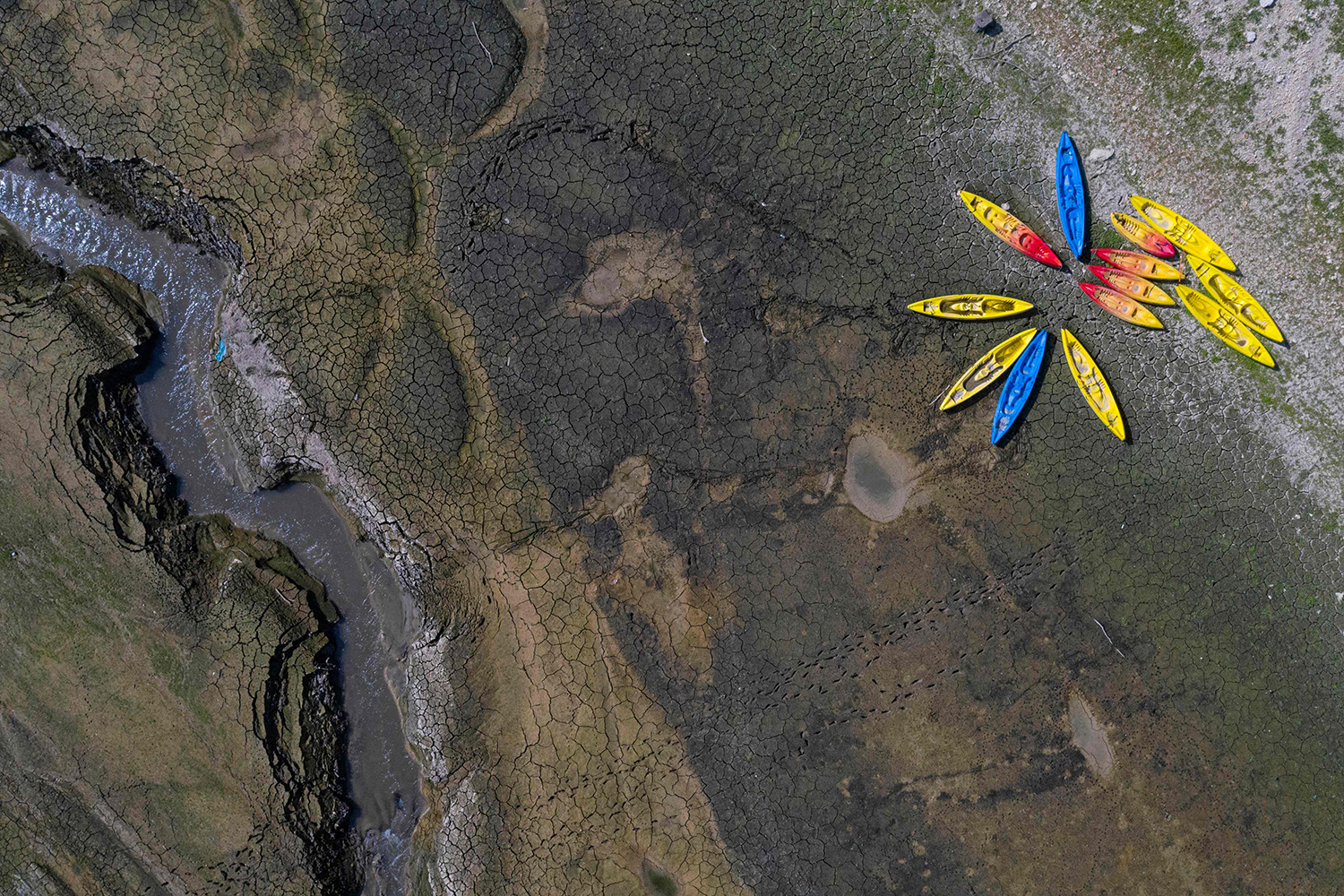 Kayaks sit on cracked earth near the dried-out Doubs river in Villers-le-Lac, eastern France, on Sept. 15. A drought in the region caused the river to be at one of its lowest levels in more than a century. SEBASTIEN BOZON/AFP via Getty Images