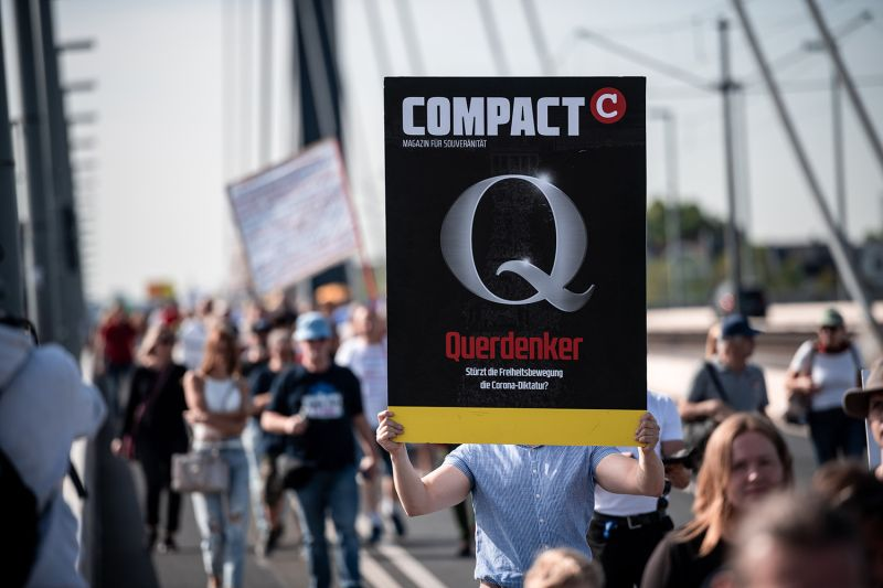 "Querdenker, or ""lateral thinker,"" is written on the sign of a participant at a march against Germany's COVID-19 measures across the Oberkassel Bridge in Düsseldorf on Sept. 20."