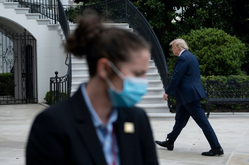 U.S. President Donald Trump walks into the White House.
