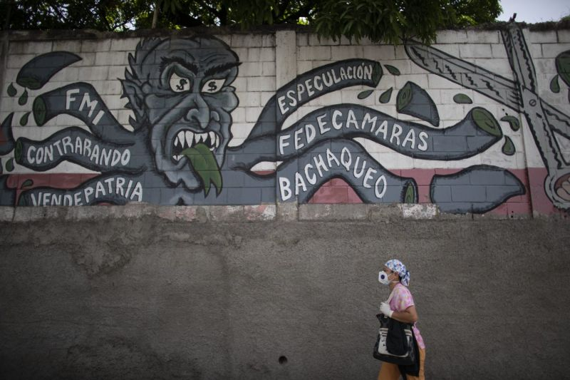 A nurse in Caracas passes an anti-imperialism mural