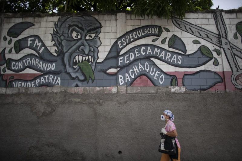 A nurse in Caracas passes an anti-imperialism mural