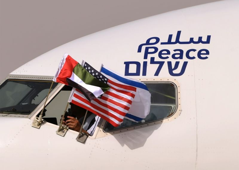 "An airplane of Israel's El Al is adorned with the Emirati, Israeli, and U.S. flags and the word ""peace"" in Arabic, English, and Hebrew on arriving at the Abu Dhabi airport in the first-ever commercial flight from Israel to the UAE on Aug. 31, 2020."