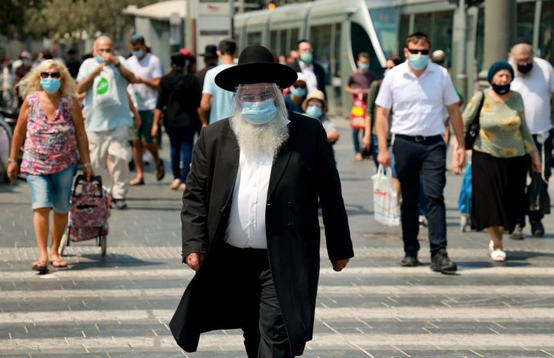 An ultra-Orthodox Jewish man wearing a protective mask and shield against the coronavirus,  walks along a street in Jerusalem on Sept 11.