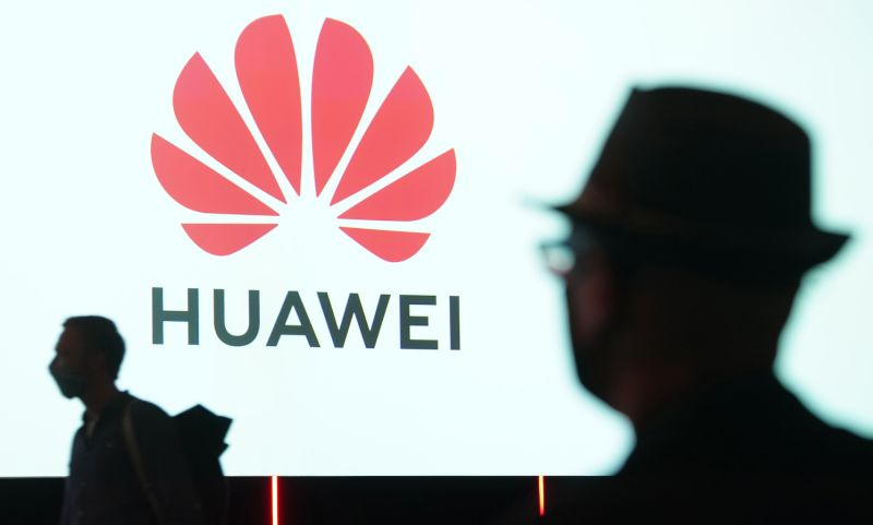 People pass a Huawei logo at a trade fair in Berlin