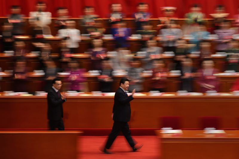 China's President Xi Jinping waves to delegates as they arrive for the opening ceremony of the 11th National Women's Congress at the Great Hall of the People near Tiananmen Square on October 28, 2013 in Beijing.