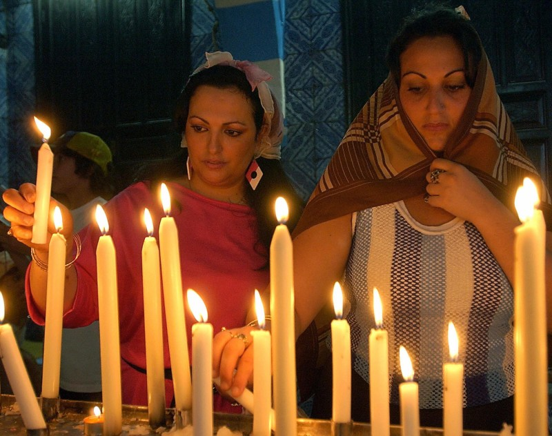 Two members of Tunisia's Jewish community, one of the largest in the Arab world, light candles 09 May 2004 in the Ghriba synagogue, on the isle of Djerba, on the second day of the annual pilgrimage there.