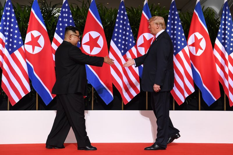 US President Donald Trump (R) and North Korea's leader Kim Jong Un (L) reach out to shake hands at the start of their historic US-North Korea summit, at the Capella Hotel on Sentosa island in Singapore on June 12, 2018. (SAUL LOEB/AFP via Getty Images)