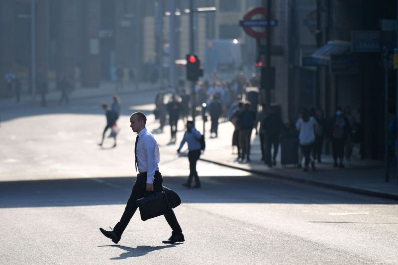 A commuter crosses a road by London Bridge in London on Sept. 15.
