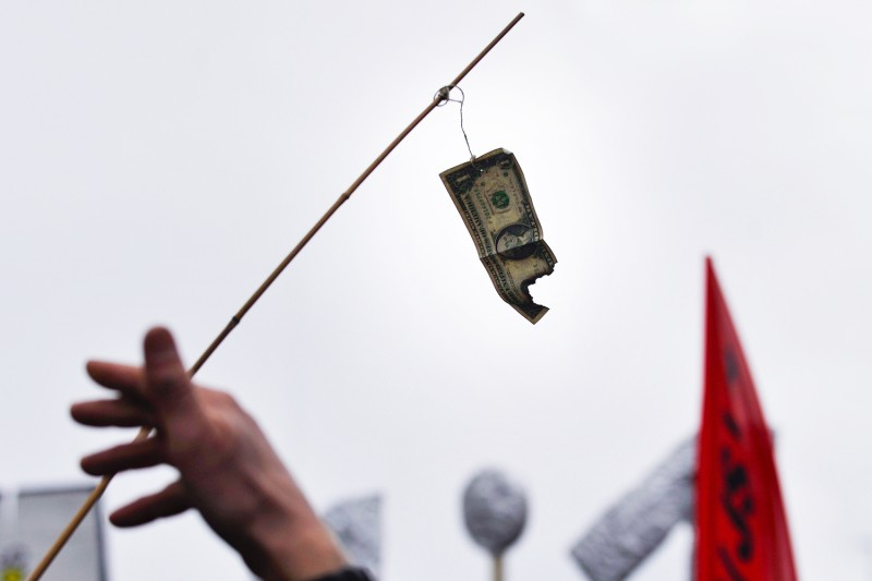 A demonstrator holds a U.S. dollar bill burned during a protest of the annual meeting of the World Economic Forum in Davos, Switzerland, on Jan. 30, 2010.