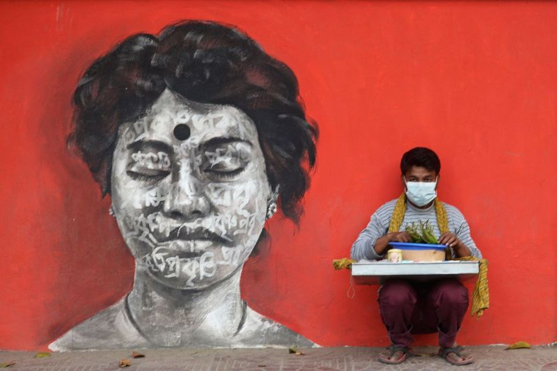 A street vendor wearing a face mask sells cigarettes on a street in Dhaka, Bangladesh, on March 12.