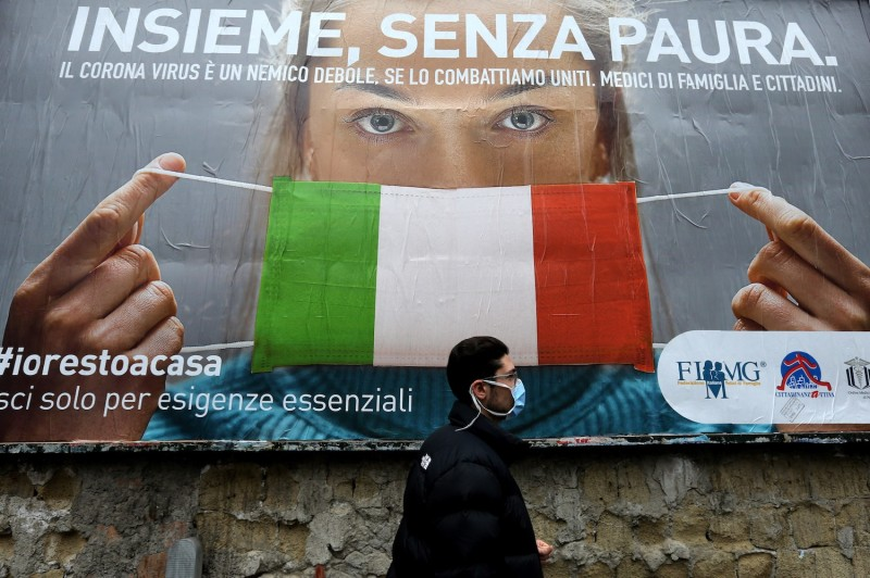 "A man walks past a large billboard showing a woman wearing Italy's national flag as a face mask and the headline ""All together, without fear,"" in Naples, Italy, on March 22."