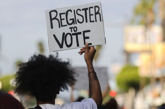 """A protester carries a """"Register to Vote"""" sign during a peaceful demonstration against police brutality in Los Angeles on June 6."""