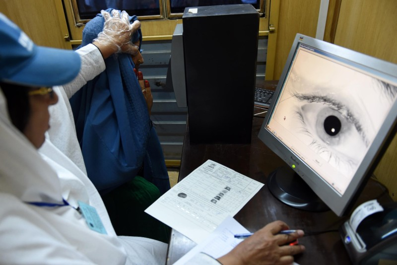 An employee at the United Nations High Commissioner for Refugees scans the eye of an Afghan refugee at the UNHCR registration center in Peshawar, Pakistan on June 23, 2016.