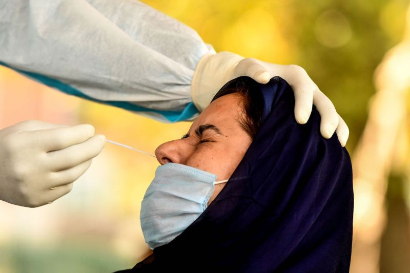 A woman reacts as a medical worker collects a swab sample for a Rapid Antigen Test for the novel coronavirus in Srinagar, Jammu and Kashmir, on Sept. 11.