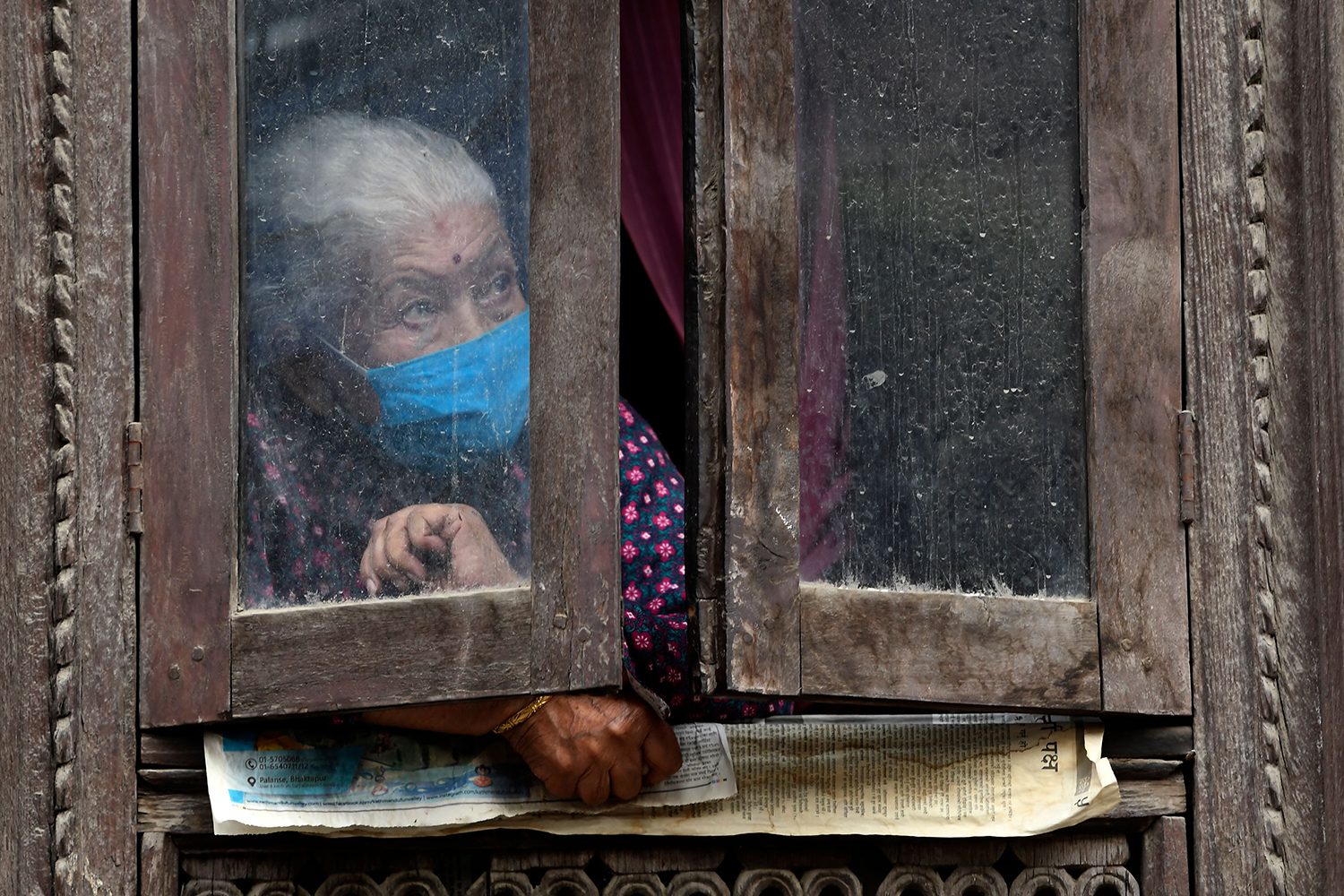 From her window, a devotee watches the Rato Machindranath Jatra Chariot festival in Lalitpur, Nepal, on Sept. 6. The centuries-old procession was supposed to begin at the end of April but was delayed when a nationwide coronavirus lockdown was imposed March 24. Although restrictions were eased in July, curbs were imposed again Aug. 20 as coronavirus cases surged. Only essential services are allowed on the streets. PRAKASH MATHEMA/AFP via Getty Images