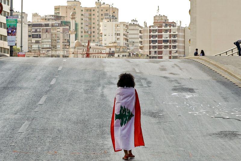 A Lebanese woman draped in a national flag