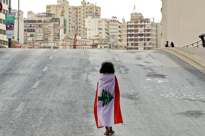 A Lebanese woman draped in a national flag