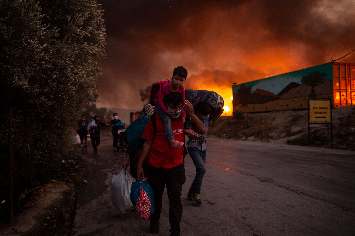 People with children flee flames after a major fire breaks out in the Moria migrant camp on the Greek Aegean island of Lesbos on Sept. 9. A fast-moving fire destroyed much of the camp, leaving most of its 12,000 residents homeless. ANGELOS TZORTZINIS/AFP via Getty Images