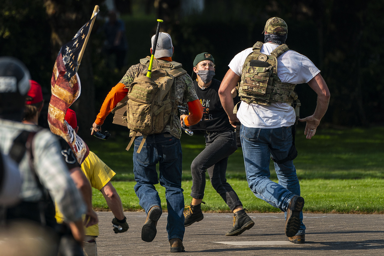 Right-wing demonstrators chase a Black Lives Matter protester after a pro-Trump caravan rally convened at the Oregon State Capitol building in Salem on Sept. 7. David Ryder/Getty Images