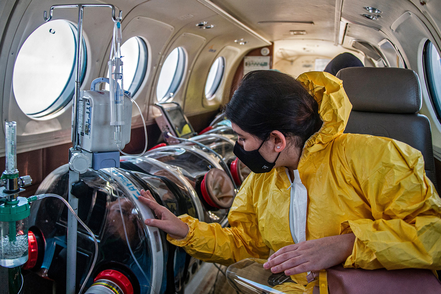Andrea Lara looks at her father, Juan Carlos Lara, 59, a patient with COVID-19, as he is transferred inside a security capsule on an air ambulance from Iquitos, Peru, to Rebagliati Hospital in Lima on Sept. 1. ERNESTO BENAVIDES/AFP via Getty Images