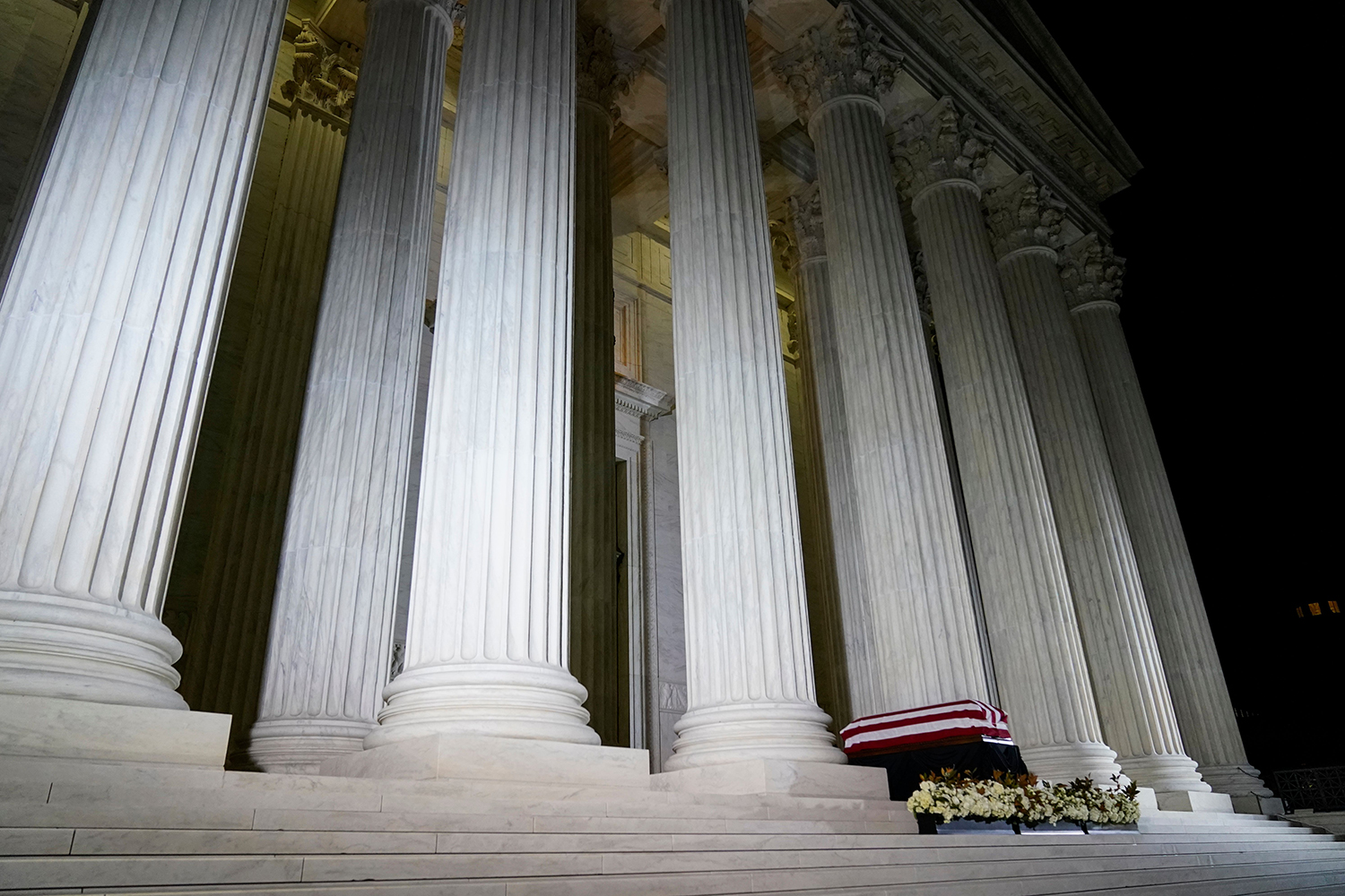 The flag-draped casket of Justice Ruth Bader Ginsburg lies in repose under the portico at the top of the front steps of the U.S. Supreme Court building in Washington on Sept. 23. ANDREW HARNIK/POOL/AFP via Getty Images