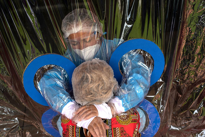 Maria Hernandez, 38, embraces her aunt through a transparent curtain at a Hogar Jardin de los Abuelitos nursing home in San Salvador, El Salvador, on Sept. 11 amid the coronavirus pandemic. YURI CORTEZ/AFP via Getty Images