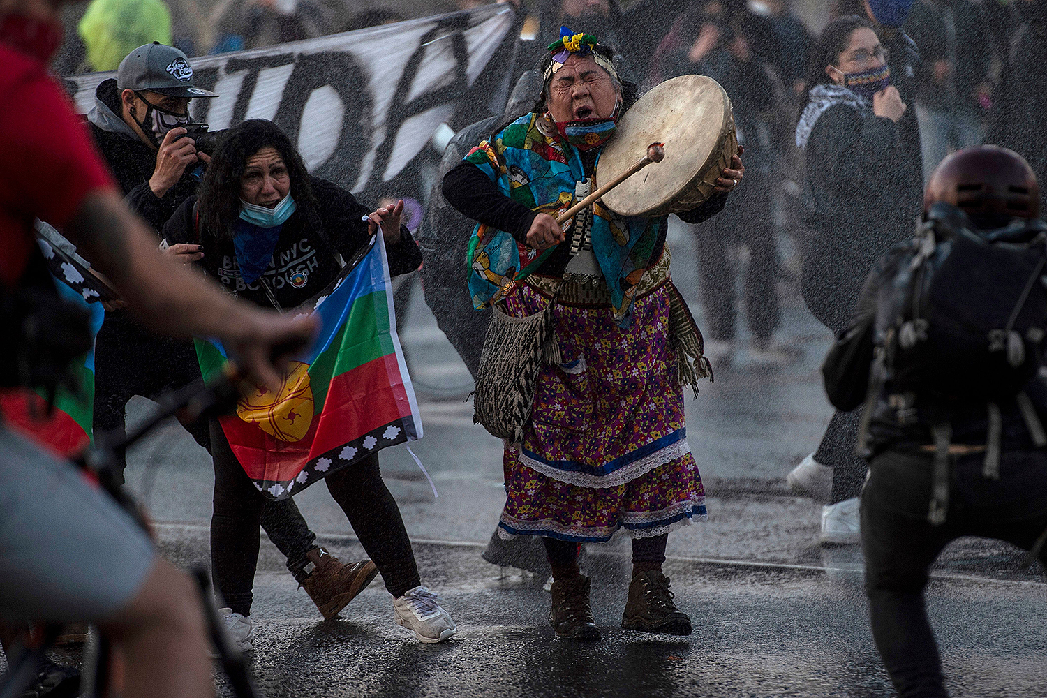 A Mapuche Indigenous woman plays a drum as riot police use water cannons to disperse demonstrators during a protest against the government's handling of the COVID-19 pandemic in Santiago, Chile, on Sept. 4. MARTIN BERNETTI/AFP via Getty Images