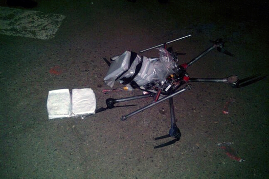 A drone loaded with packages of methamphetamine lies on the ground.