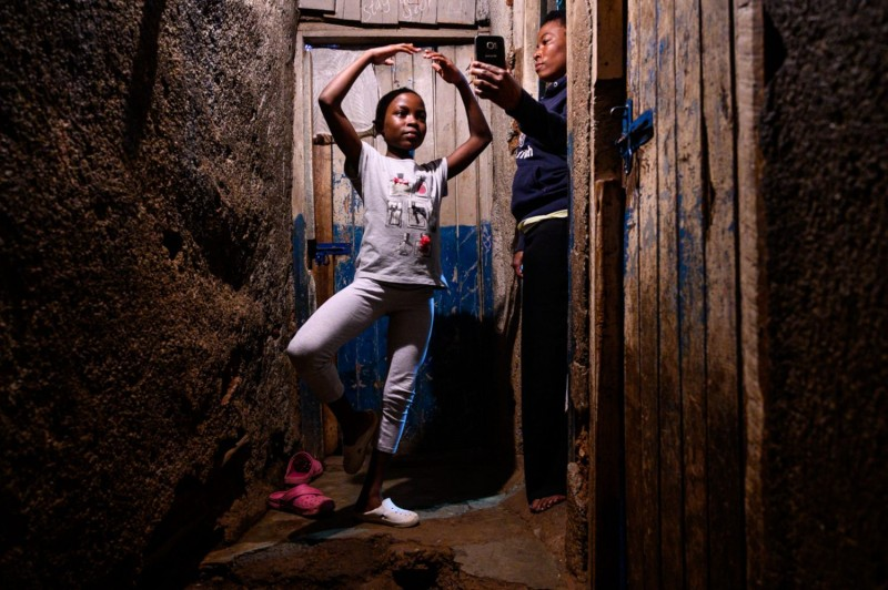 A girl practices ballet during a distant lesson via a mobile phone in Nairobi on May 22.