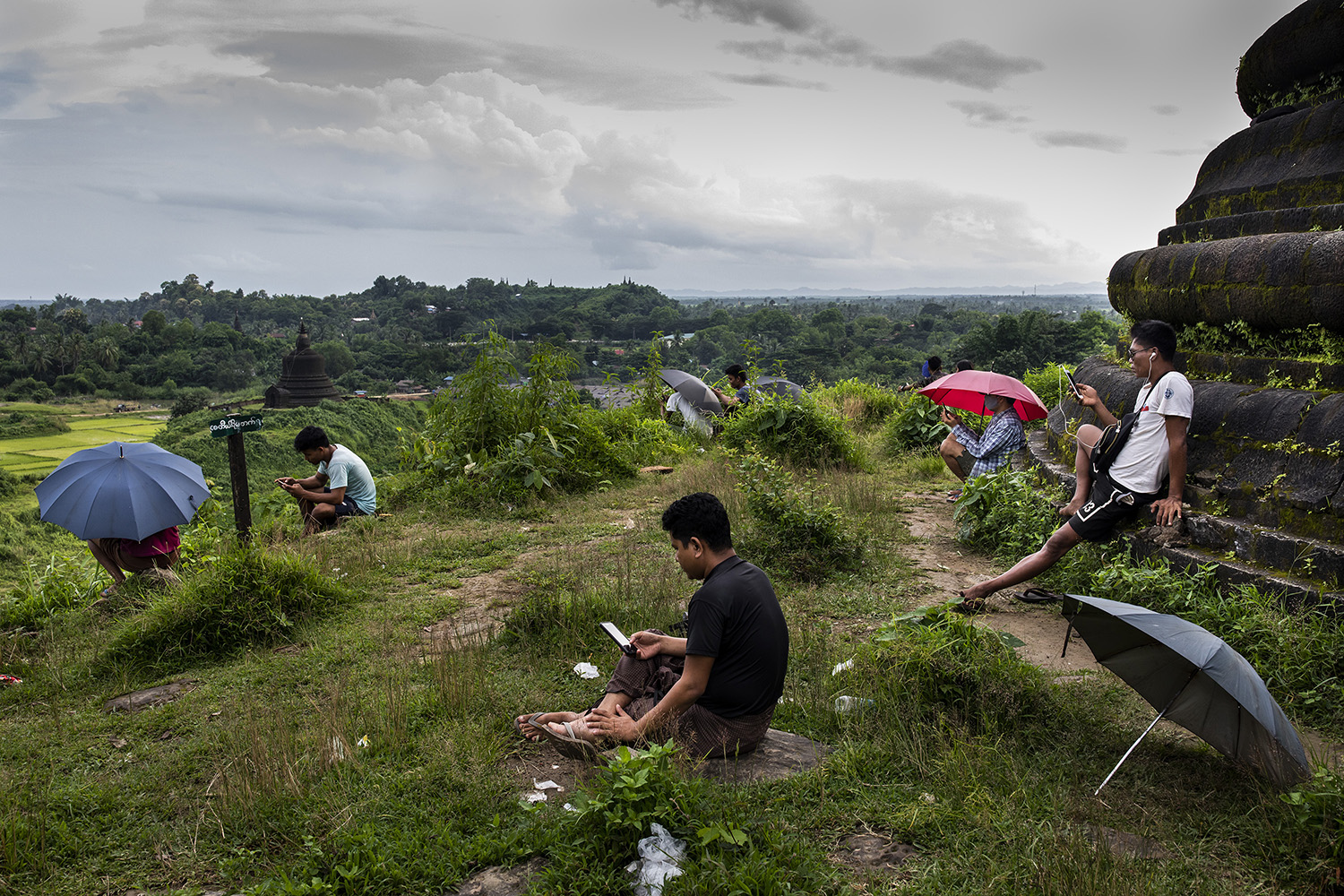 People sit on a hill to search for a 3G signal in Mrauk-U, Myanmar, on Aug. 20. The government has blocked high-speed internet in the township since June 2019.