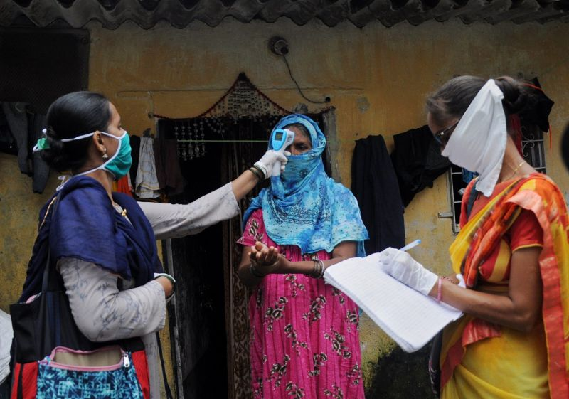 A community health care volunteer checks the temperature of a woman in Mumbai during testing for COVID-19.