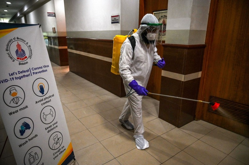 A worker sprays disinfectant.