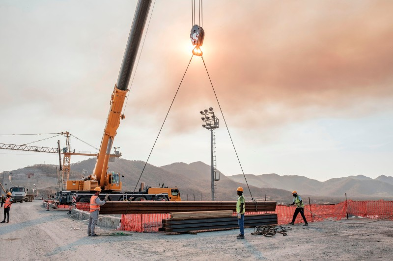 Workers move iron girders from a crane at the Grand Ethiopian Renaissance Dam, near Guba in Ethiopia, on Dec. 26, 2019.