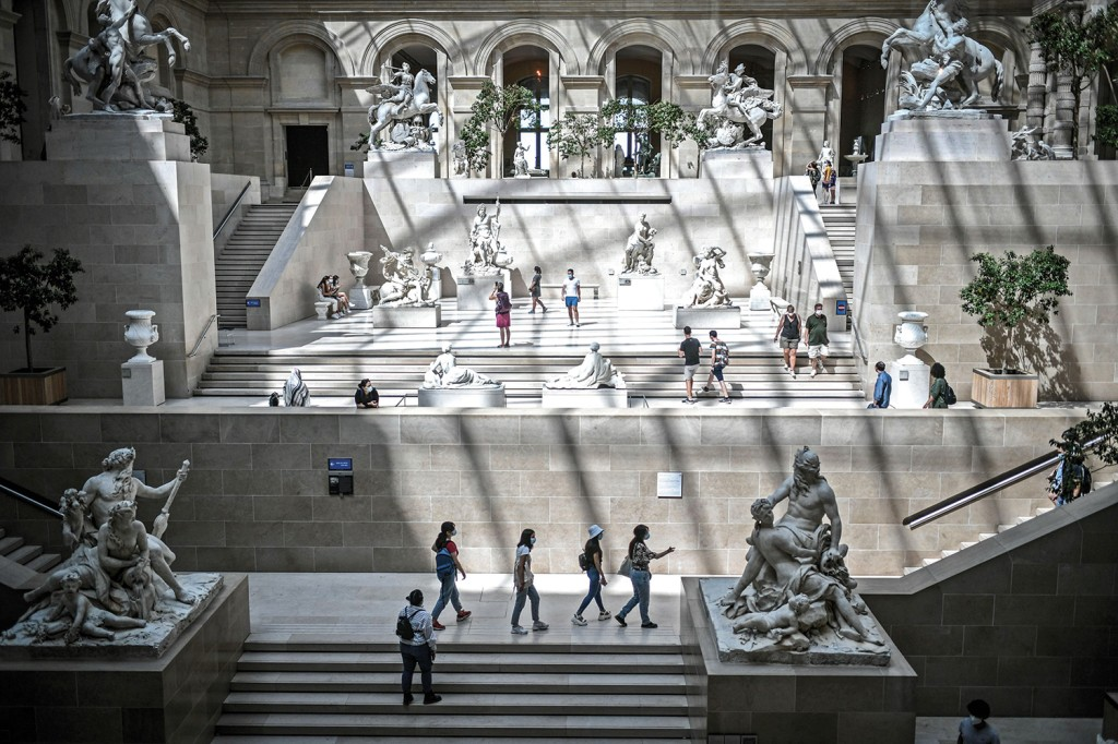 Tourists wearing protective face masks visit the Louvre in Paris on Aug. 6 after the lifting of some coronavirus  restrictions.