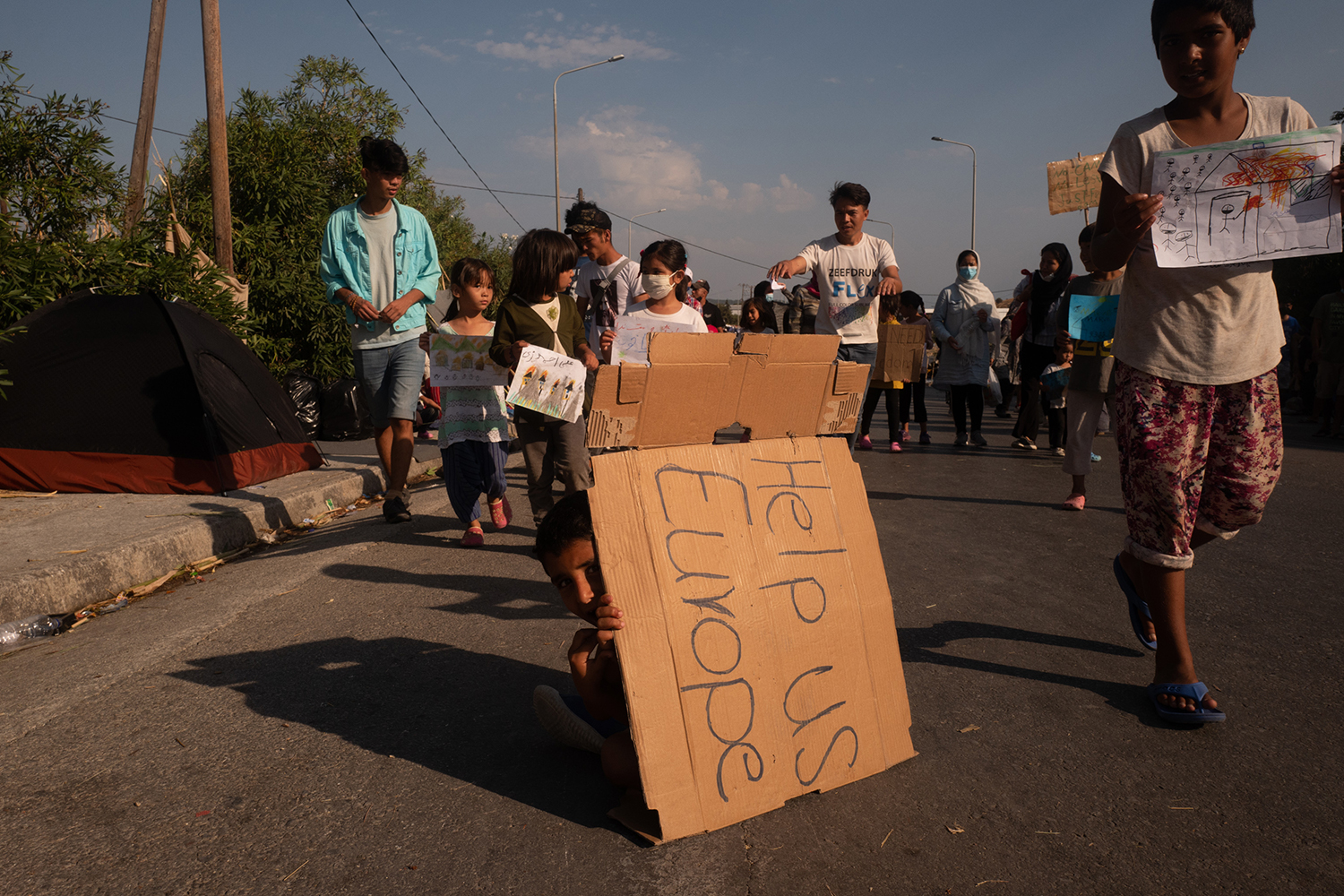 Migrant children protest in the main street connecting Moria camp to Mytilene against plans to move to a new camp on Sept. 12.